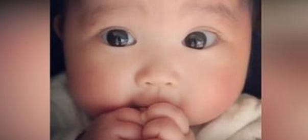 婴儿正专心吃手,突然发现妈妈在看她,宝宝的反应好可爱