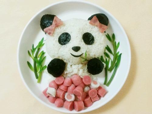10,把煎好的鸡蛋叠一半盖住大熊猫的身体,把鱼卷片放在鸡蛋上面